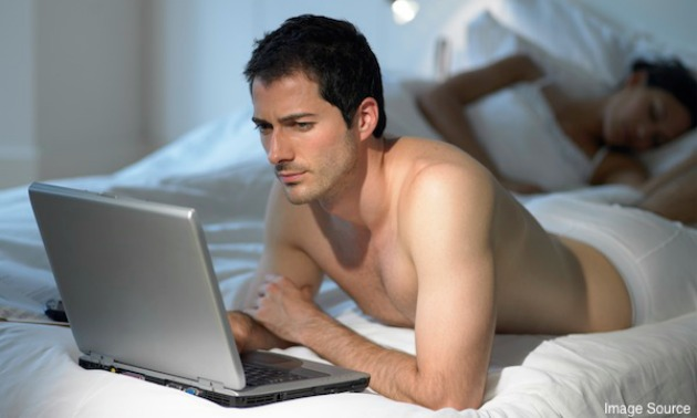 Man using laptop as wife sleeps