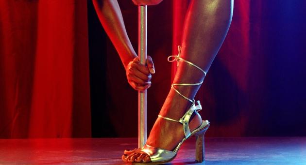 Woman pole dancer bending over, portrait