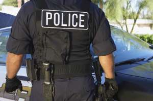 Police officer in bulletproof vest outdoors, back view
