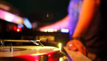 DJ at turntable in disco